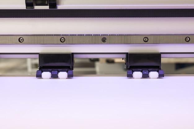 O rolo do papel vazio e roda dentro a grande máquina de jato de tinta do formato da impressora para o negócio industrial. Foto Premium