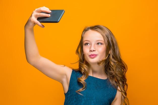 O rosto da menina adolescente feliz brincalhão com telefone Foto gratuita