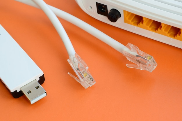O roteador de internet, o adaptador usb wi-fi portátil e os plugues de cabo de internet encontram-se em um fundo laranja brilhante. itens necessários para conexão com a internet Foto Premium