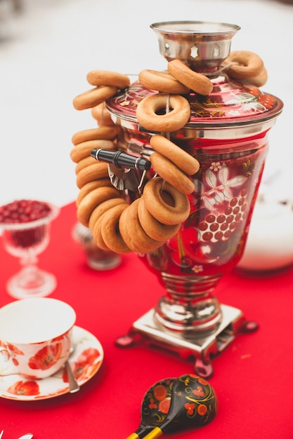 O russo tradicional bronzeou o samovar pintado em um tablecloth vermelho, um símbolo da hospitalidade. bagels crocantes, secagem ou bagels pendurar no samovar Foto Premium