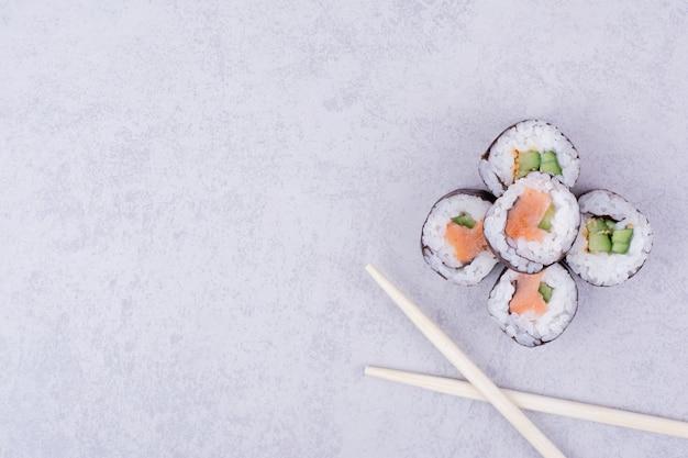 O saquê maki rola com salmão e abacate no cinza. Foto gratuita