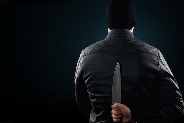 O serial killer, um maníaco com uma faca e um chuolkom preto na cabeça Foto Premium