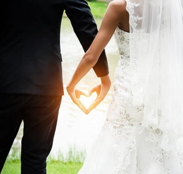 O sinal de mão de amor feito pelo noivo e noiva Foto Premium