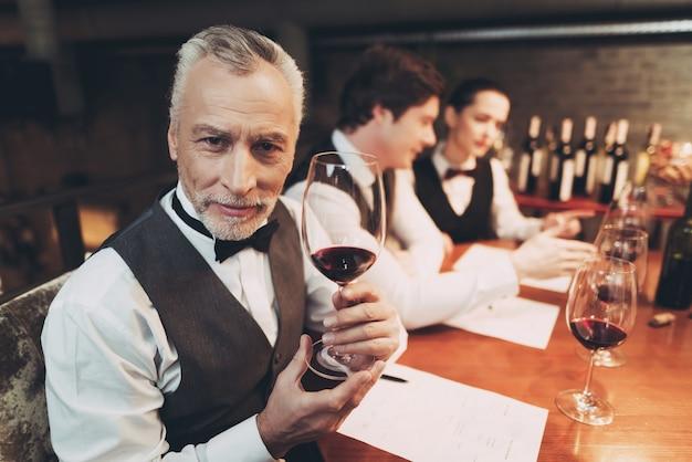 O sommelier experiente velho está prendendo o vidro do vinho vermelho. Foto Premium