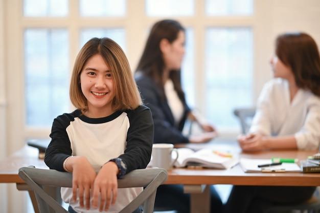 O sorriso da jovem mulher no rosto com retrato disparou na biblioteca do campus. Foto Premium