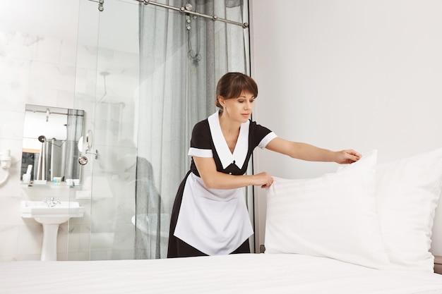 O sorriso do cliente me faz sentir melhor. fêmea de uniforme de empregada fazendo a cama no quarto, colocando o travesseiro depois de lavá-lo anteriormente. empregada doméstica tentando terminar com a limpeza antes que os proprietários da casa retornem Foto gratuita