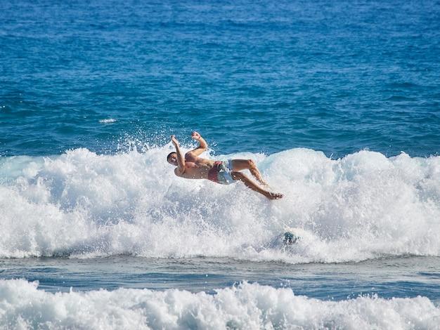 O surfista na onda apaga e cai da prancha de surf. Foto Premium