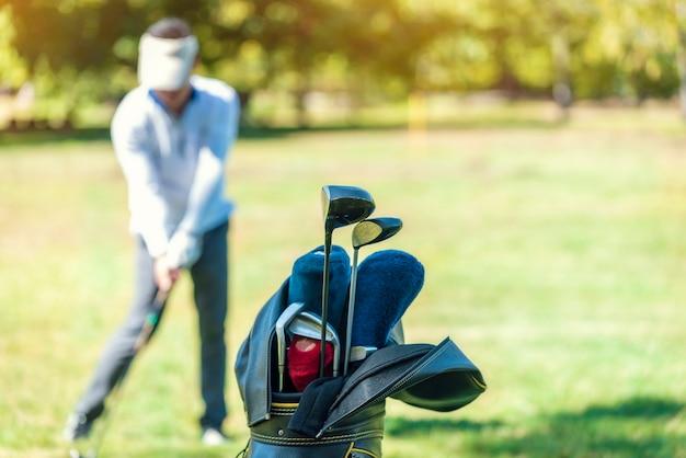O taco de golfe é armazenado em um bolso com golfistas no gramado como o fundo desfocado. Foto Premium