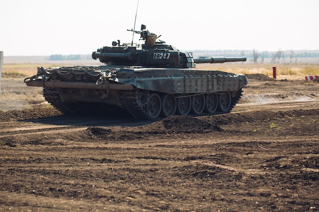 O tanque blindado monta em off-road. exercícios de tanque no campo. Foto Premium