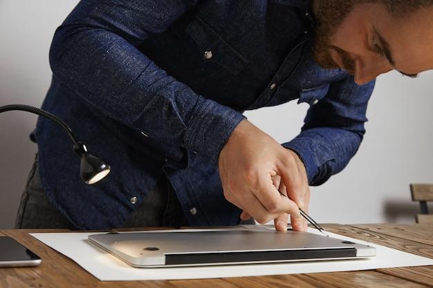 O técnico coloca pequenos parafusos no buraco com pinças anguladas para fechar a parte superior traseira do laptop do computador pessoal após o serviço de reparo e limpeza em seu laboratório Foto gratuita