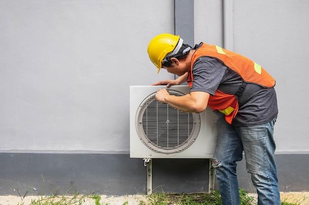 O técnico está consertando o ar condicionado. Foto Premium