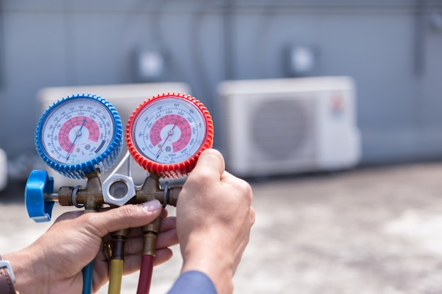 O técnico está verificando o condicionador de ar, equipamento de medição para encher condicionadores de ar. Foto Premium