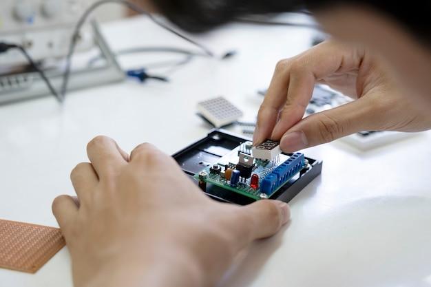 O técnico verifica o dispositivo eletrônico. Foto Premium