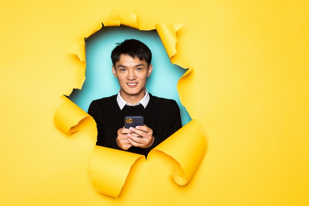 O telefone móvel novo da posse do homem chinês mantém a cabeça no furo da parede amarela rasgada. cabeça masculina em papel rasgado. Foto gratuita