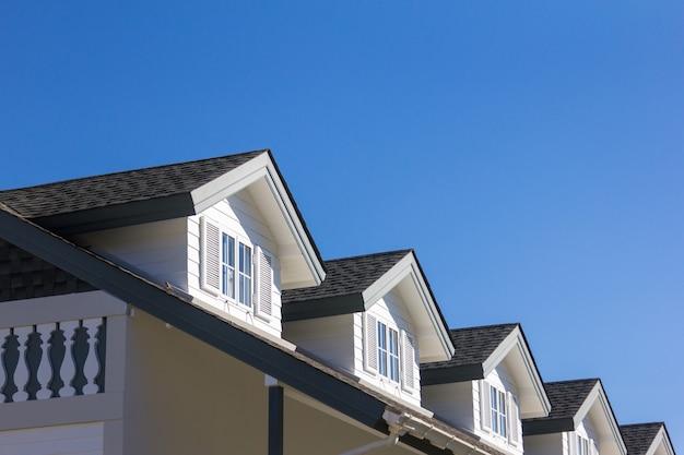 O telhado da casa com a janela bonita no fundo do céu azul. Foto Premium