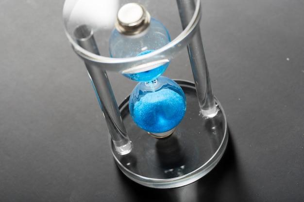 O tempo está passando. ampulheta azul close-up Foto Premium