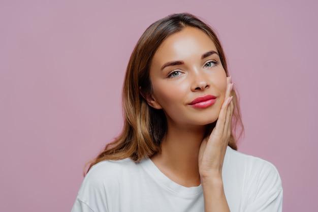O tiro na cabeça da adorável modelo feminina toca suavemente a bochecha, desfruta da pele delicada do rosto Foto Premium
