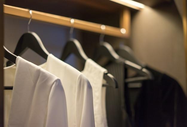 O tom preto e branco da cor veste a suspensão no trilho em um vestuário, design de interiores. Foto Premium