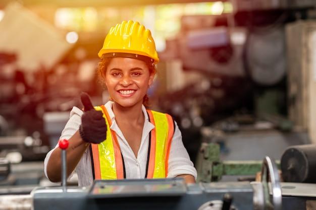O trabalhador adolescente da menina com capacete de segurança mostra o polegar acima trabalhando como trabalho na fábrica da indústria com máquina de aço. Foto Premium