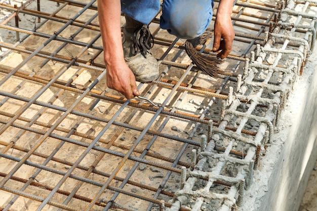 O trabalhador amarra barras de reforço de aço com fio. Foto Premium