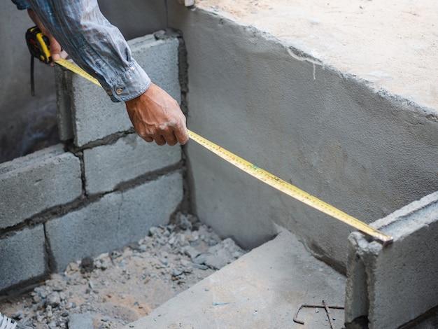 O trabalhador da construção profissional usa a fita de medição para a medida e colocando tijolos com cimento. Foto Premium