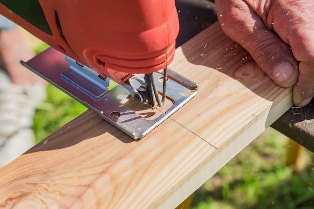 O trabalhador de madeira que corta o painel de madeira com gabarito viu ao ar livre Foto Premium