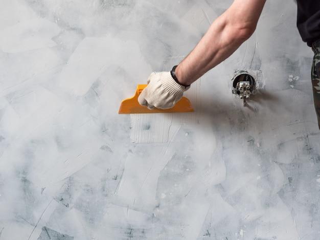 O trabalhador entrega guardar uma espátula com massa de vidraceiro branca. reparação e renovação em casa. novo design de interiores. Foto Premium