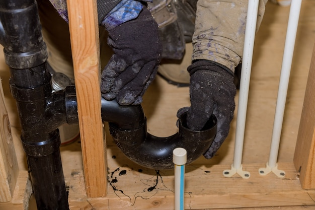 O trabalhador está usando cola com encaixe para instalar o tubo de drenagem de pvc na área de trabalho. Foto Premium