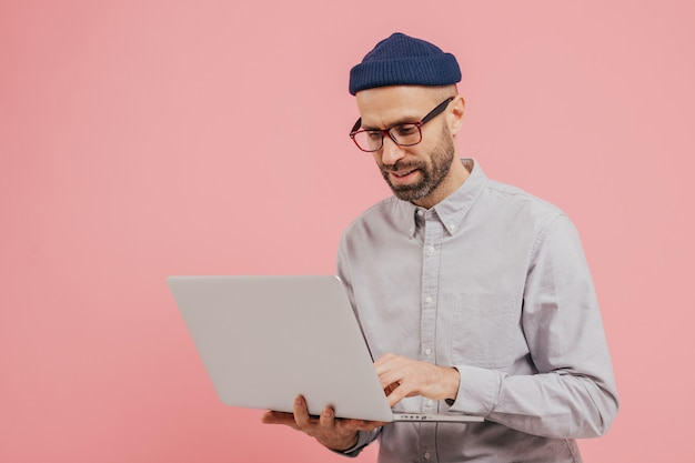 O trabalhador profissional masculino procura um filme interessante para assistir, usa o gadget, digita informações no computador laptop Foto Premium