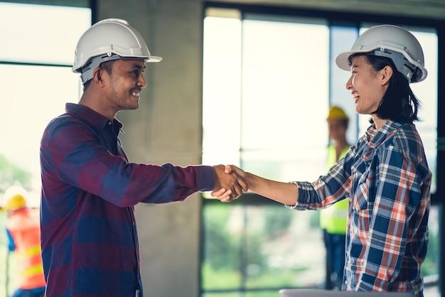 O trabalho de equipa do oficial está feliz e agita as mãos para comemorar no edifício home do sucesso constructi Foto Premium