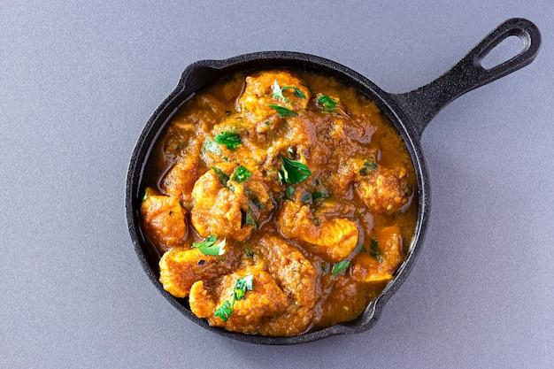 O tradicional curry de frango com manteiga indiana e limão serviram ferro fundido. vista do topo. cozinha tradicional do mundo. Foto Premium