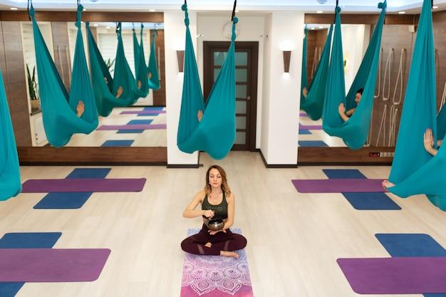 O treinador ioga com a taça da meditação introduz suas proteções em transe. mosca ioga exercícios de alongamento no ginásio. estilo de vida apto e bem-estar Foto Premium