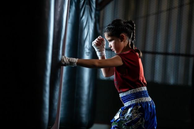 O treinamento tailandês pequeno do encaixotamento da menina é um curso da autodefesa, muay thai. Foto Premium