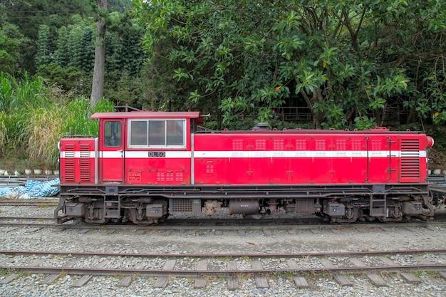 O trem vermelho velho na linha de alishan (para baixo) volta à estação de trem de chiyi no dia nevoento. Foto Premium