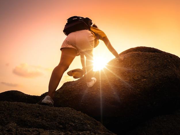 O turista da moça está escalando à parte superior da rocha. alpinista de mulher com mochila sobe terreno rochoso íngreme. Foto Premium