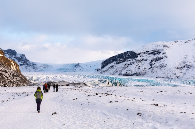 O turista dirige-se à geleira no panorama da geleira das montanhas islandesas Foto Premium