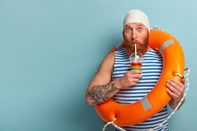 O turista envergonhado bebe um coquetel frio de verão, passa o tempo livre na praia, usa uma camiseta de marinheiro com touca Foto gratuita