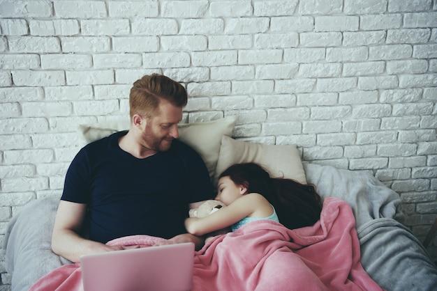 O único pai de cabelo vermelho trabalha com portátil. Foto Premium