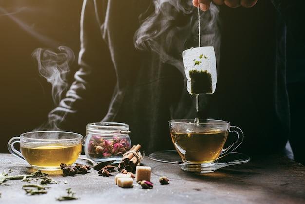 O vapor do homem com jecket jean está ensopando o saquinho de chá na xícara branca vintage, preparando o chá quente. Foto Premium