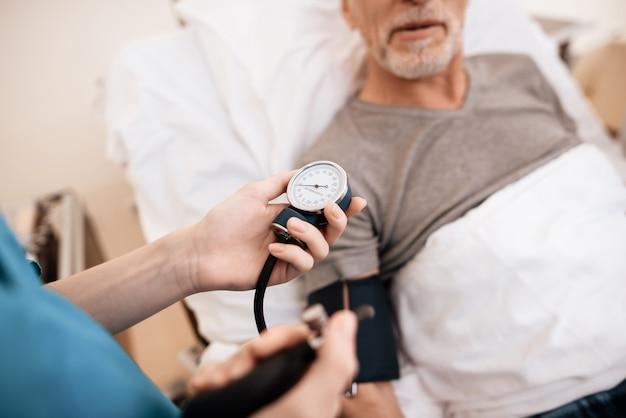 O velho encontra-se em uma cama na enfermaria, a enfermeira mede a pressão. Foto Premium