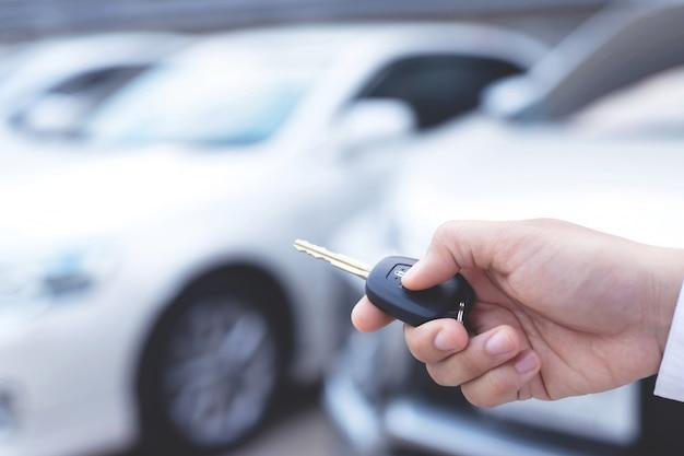 O vendedor está abrindo e fechando a porta do carro com a chave. Foto Premium