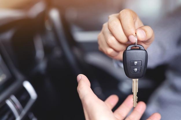O vendedor está entregando as chaves do carro novo ao cliente no showroom. Foto Premium