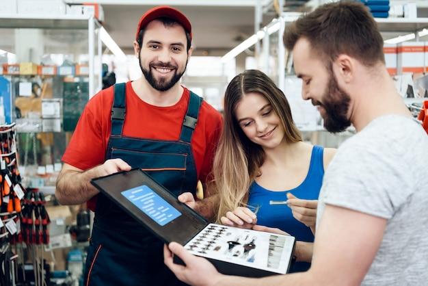 O vendedor está mostrando a pares de novos clientes a caixa de ferramentas. Foto Premium