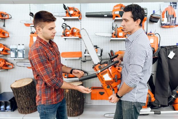 O vendedor na loja mostra aos clientes uma motosserra. Foto Premium