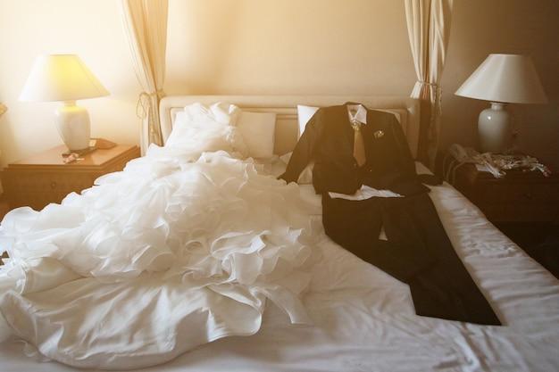 O vestido e o terno de casamento que encontram-se na cama branca com sol bonito iluminam-se na sala de hotel. dia dos namorados e amor para o conceito de celebração. Foto Premium