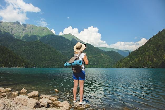 O viajante bonito da menina em um chapéu está em um lago no fundo das montanhas Foto Premium