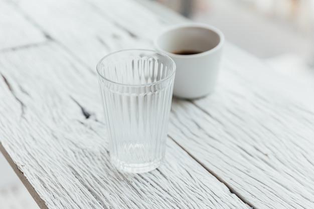 O vidro desobstruído e uma chávena de café no branco pintaram a tabela de madeira. Foto Premium