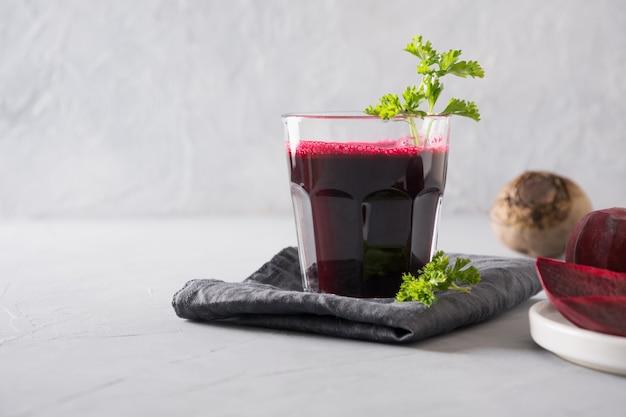 O vidro do suco de beterrabas fresco decora a salsa no cinza. Foto Premium