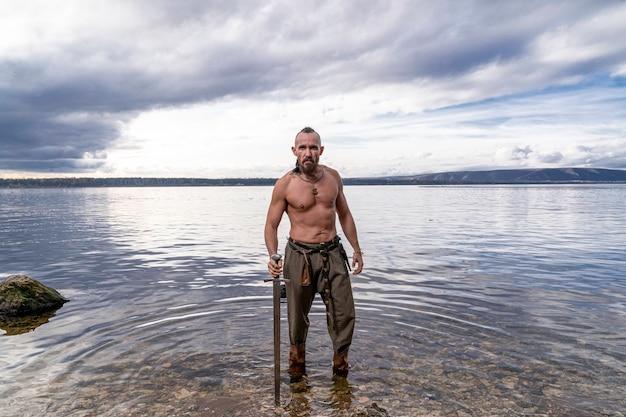 O viking com uma espada nas mãos está contra o fundo do rio e do céu Foto Premium
