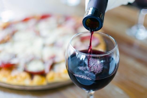 O vinho tinto é despejado da garrafa no copo no restaurante ou no café, Foto Premium